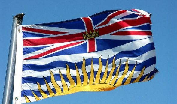 Photo of the flag of British Columbia, which depicts a sun, the ocean, and the Union Jack, flying in the wind.
