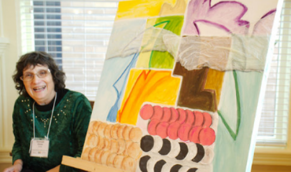 Photo of an artist posed next to her painting.