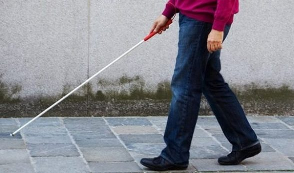 Photo of the legs of a man walking with a white cane.