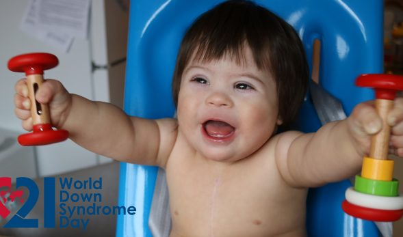 "Photo of a baby smiling, holding a toy in each hand. ""World Down Syndrome Day"" is written in the corner, with a heart-shaped logo featuring a map of the world in beside it."