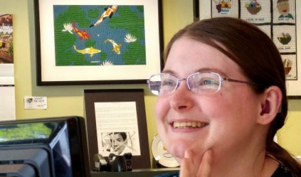 Photo of Kelsey Hampson smiling, with some of her artwork in the background.