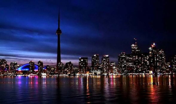 Photo of Toronto at night, with the CN tower shrouded in darkness on the left-side of the photo.