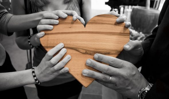 Photo of a bunch of hands holding a wooden heart, with the heart coloured and the rest of the photo in monotone.
