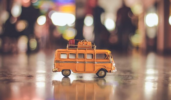 Photo of a miniature bus figurine in the foreground, with city lights in the background.