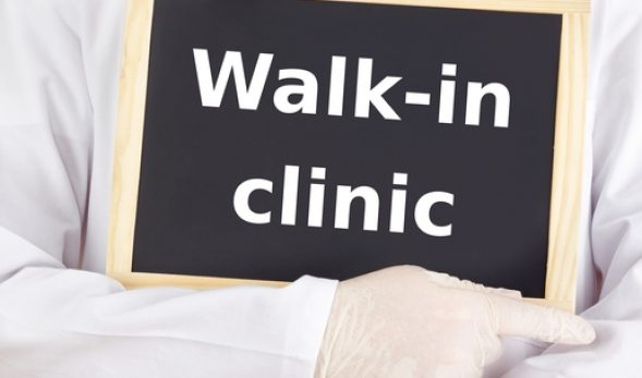 "Photo of a doctor holding a ""Walk-In Clinic"" sign."