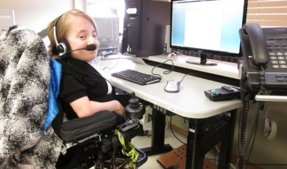 Person in power chair using microphone to operate computer
