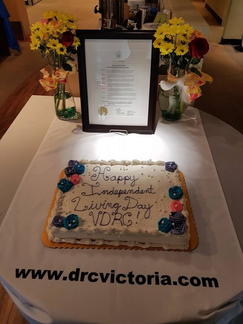 Photo of proclamation (in background) issued by City of Victoria in honour of Independent Living Across Canada, with celebration cake in foreground.