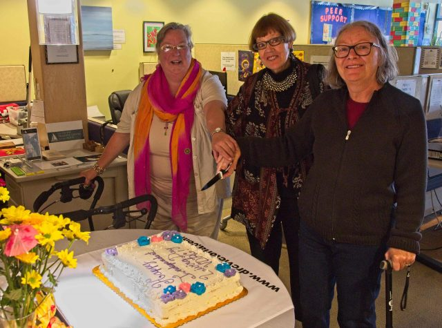VDRC Director Snow Manning-Jones, City of Victoria Councillor Pamela Madoff, VDRC Director Lynn Mullally, cutting the cake celebrating Independent Living Across Canada Day.