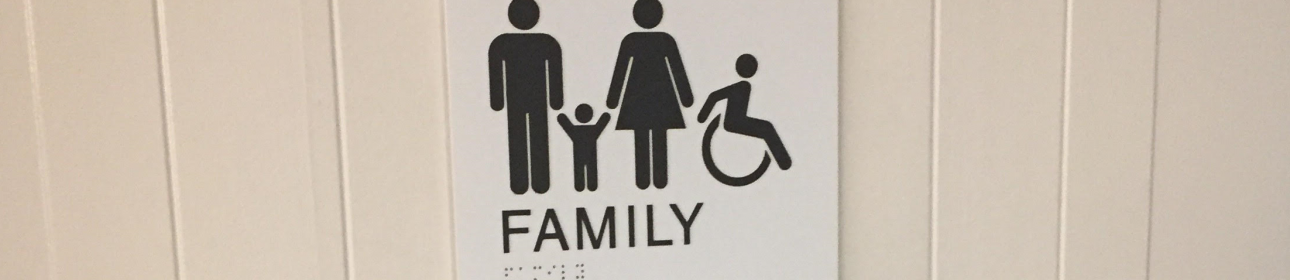 "Photo of the entrance to the Inner Harbour Public Washroom, featuring artwork of a family alongside the modern international symbol of accessibility. The word ""Family"" is written on the sign, both in English lettering and in braille."