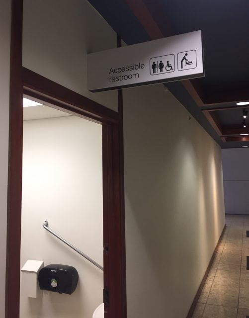 A photo of the accessible washroom inside the Royal BC Museum. The sign showcases the old international symbol of accessibility and a changing table symbol.