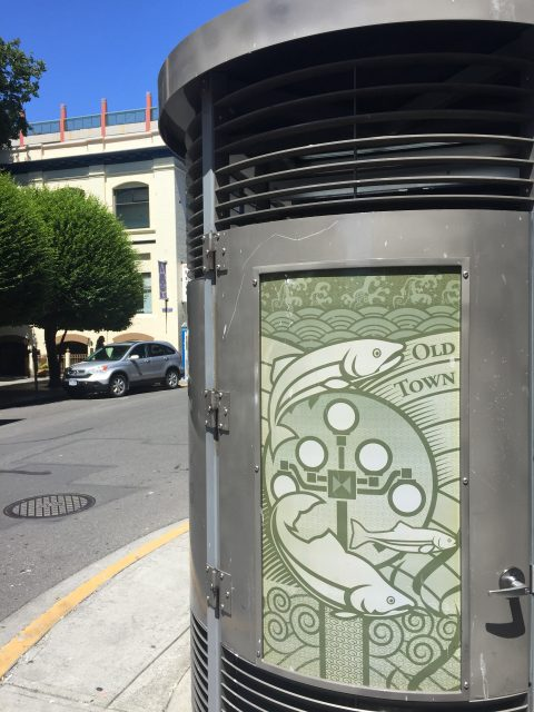 A photo of the Langley Street Loo, which is a grey hut structure with a green Salmon design on the door.