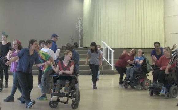 Photo of the all abilities dance on the 14th in 2018. It has people dancing with three duets smiling in the foreground.