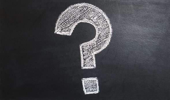 Photo of a question mark drawn in white chalk on a blackboard.